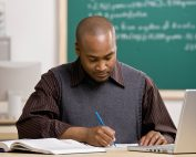 African American Male Teacher Grading Papers